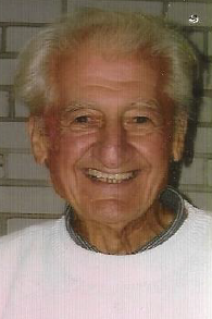 A smiling elderly man in a white sweater